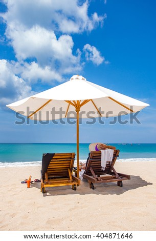 woman resting under a beach umbrella facing the seaside in a deserted beach with deep blue sky