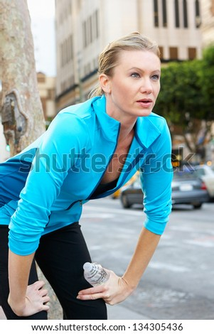 Woman Resting Whilst Running Along Urban Street