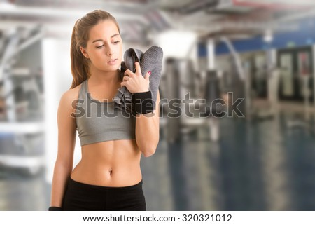 Woman resting with a towel around her neck after a fitness workout in a gym - stock photo