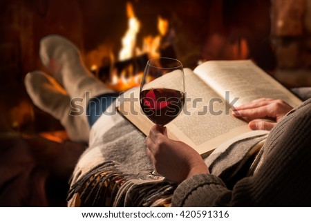 Woman resting with glass of red wine and book near fireplace - stock photo