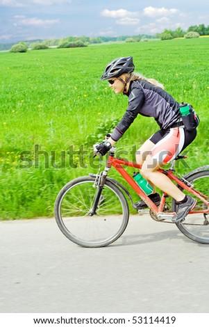 Woman ride mountain bike, motion blur. - stock photo