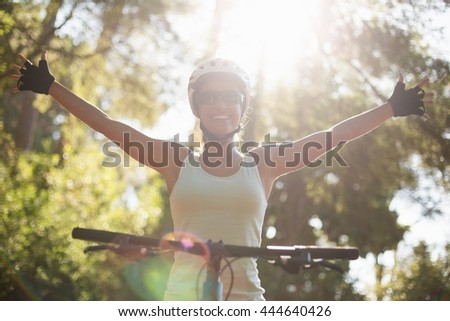 Woman rider smiling and throwing arms on the wood - stock photo