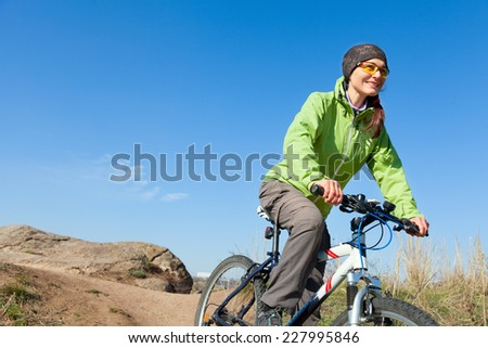 Woman riding a mountain bike down the hill looking into the distance - stock photo