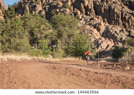 Woman Riding a Mountain Bike in Rocky Landscape. - stock photo