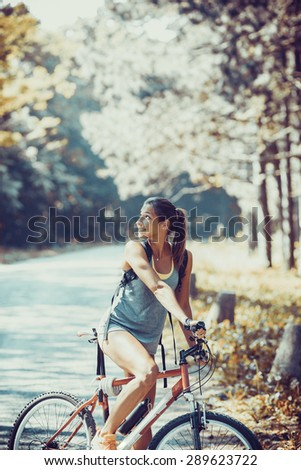 Woman riding a mountain bike in the forest.Grain effect added for artistic impression. - stock photo