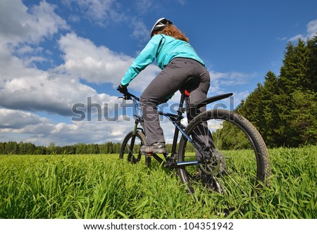woman riding a mountain bike on a background of the blue sky - stock ...