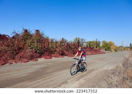 Woman riding a mountain bike on a rural  road - stock photo