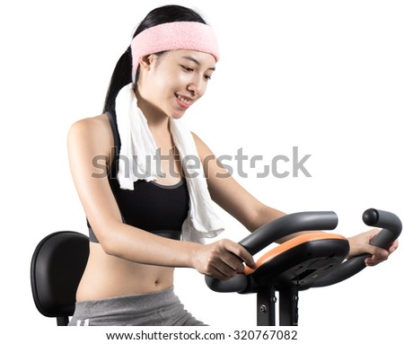 Woman riding an exercise bike in gym or home ,copy space , isolated - stock photo