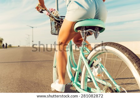 Woman riding bicycle. Close-up rear view image of young women riding on her bicycle along the road - stock photo