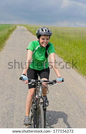 Woman riding bike on cycling path in the countryside meadow - stock photo