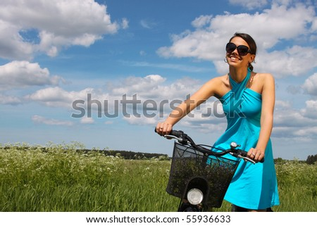 woman riding bike through a field - stock photo