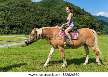 Woman riding horse - stock photo