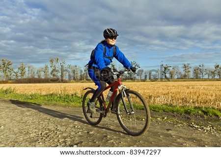 Woman riding mountain bike in autumn. Cycling in nature