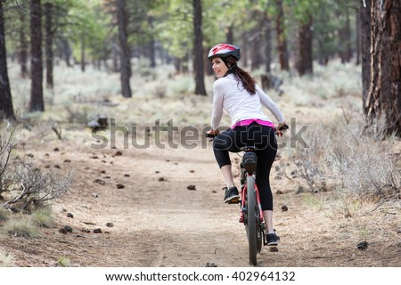 Woman riding mountain bike on trail in forest