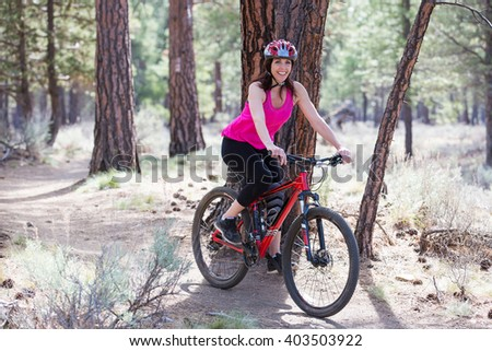 Woman riding mountain bike on trail in forest - stock photo