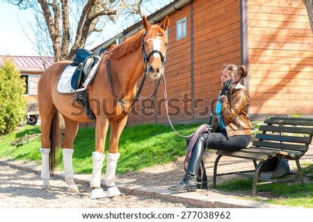 Woman riding trainer near chestnut horse speaking on cell phone. Multicolored outdoors image. - stock photo