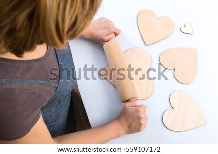 woman rolling fake wooden heart shaped cookies on white background