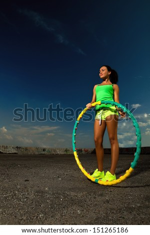 woman rotates hula hoop against blue sky  - stock photo