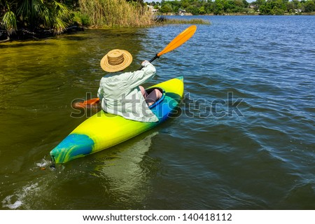 Woman rowing away from shore in her kayak on a beautiful river or lake. - stock photo