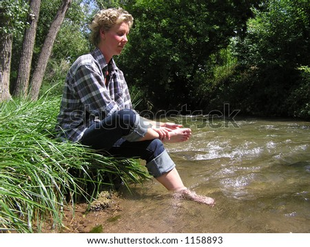 Woman rubbing feet by stream - stock photo