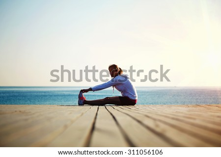 Woman runner doing exercises for the muscles of the body after an active run - stock photo