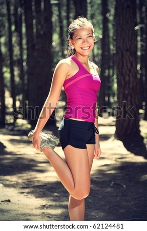 Woman runner doing workout stretching out outdoors in forest. Beautiful sunny day. - stock photo