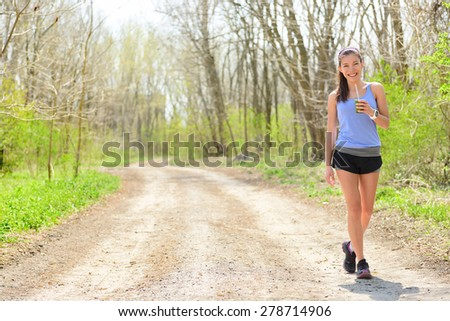 Woman runner drinking green smoothie wearing smartwatch. Female runner resting drinking a spinach and vegetable smoothie taking a break walking and resting during outdoor running workout in forest. - stock photo