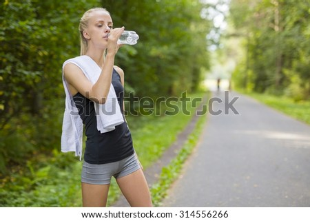 Woman runner drinking water after running - stock photo