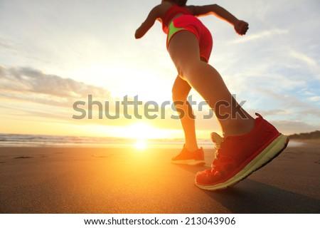 Woman Runner feet running on the beach at sunrise closeup on shoe. woman fitness sunrise jog workout wellness concept. asian - stock photo