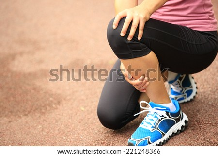 woman runner hold her injured knee - stock photo