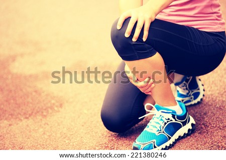 woman runner hold her injured knee  - stock photo