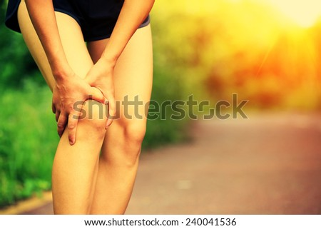 woman runner hold her injured leg  - stock photo