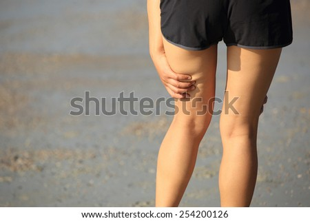 woman runner hold her sports injured legs - stock photo