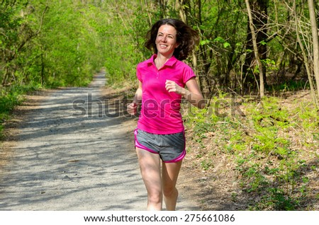 Woman runner jogging outdoors in forest, exercising, sport and fitness concept  - stock photo