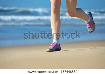 Woman runner legs in shoes on beach, running and sport concept