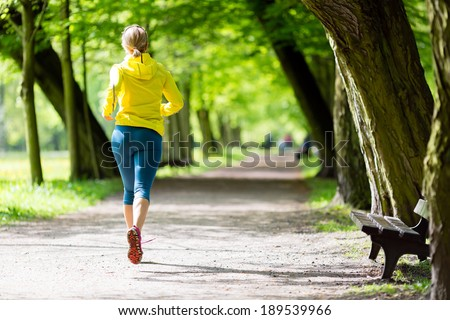Woman runner running and walking in park, summer nature, exercising in bright forest outdoors - stock photo