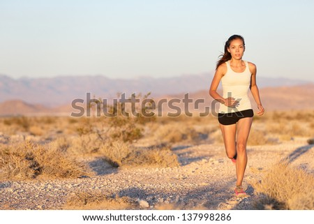 Woman runner running cross country trail run. Female jogger training outside on path outdoors at summer sunset. Beautiful young fitness model with healthy lifestyle . Mixed race Asian Caucasian girl. - stock photo