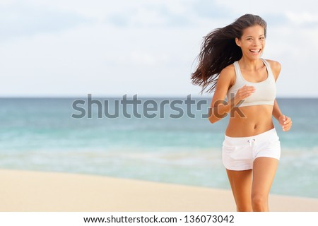 Woman runner running happy on beach laughing having fun while jogging and training for marathon run. Beautiful young mixed race Chinese Asian Caucasian female fitness model working out outside. - stock photo