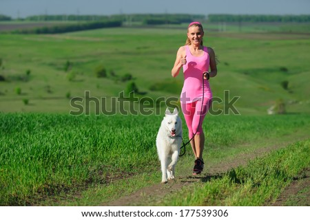 Woman runner running with dog on country road in summer nature, fitness and exercising outdoors, motion blur. Cross country running with friend. - stock photo