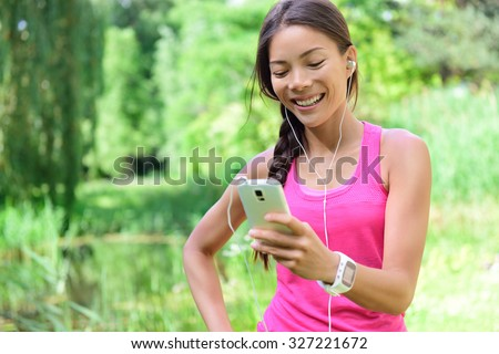 Woman runner sharing running data on social media after exercise. Girl listening to music on smart phone after jogging run in city park. Female jogger with earphones, smartphone and heart rate monitor - stock photo