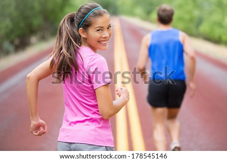 Woman runner smiling looking at camera. Couple running together training outdoors on red road in summer. Beautiful young multiracial Asian Caucasian female fitness sports model. - stock photo