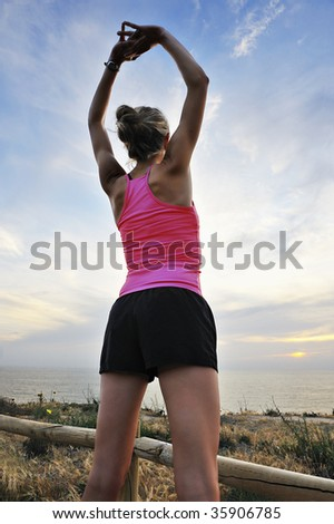 Woman runner stretches at the end of a run, sunset in background