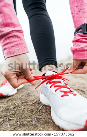 Woman runner tying sport shoes. Walking or running legs, autumn adventure and exercising outdoors. Young female hiker ready to hike. Motivation and inspiration fitness concept outside nature. - stock photo