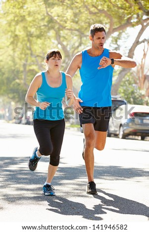 Woman Running Along Street With Personal Trainer - stock photo