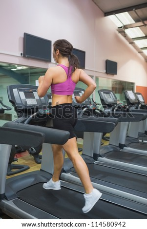 Woman running and training on a treadmill in a gym wearing black shorts and purple top