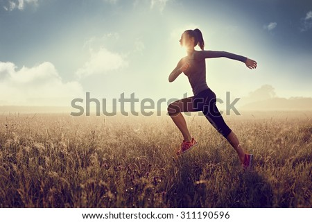 woman running at morning during sunset -  silhouette - stock photo