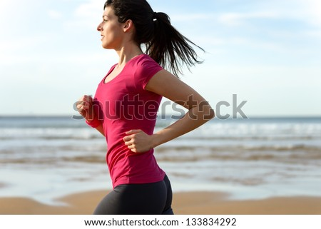 Woman running fast on beach at sunset. Brunette fitness girl runner exercising outdoors on sea background. Caucasian female athlete training.