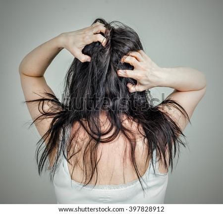 Woman running her fingers through her hair scratching the back of her head.