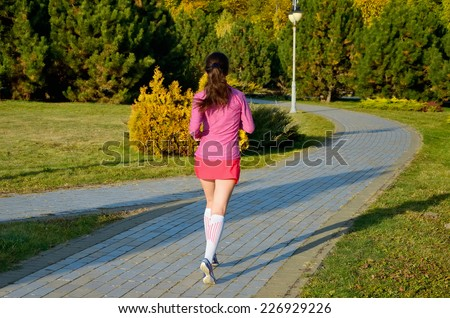 Woman running in autumn park, beautiful girl runner jogging outdoors, back view, training for marathon, exercising and fitness concept  - stock photo