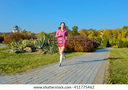 Woman running in autumn park, beautiful girl runner jogging outdoors, training for marathon, exercising and fitness concept